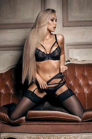 mujer desnuda sentada: mujer sexy en ropa interior negro seductora sentada en un sof� en medias