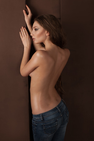 black breast: sexy topless woman in jeans, in oil, stands near wall, fashion shoot
