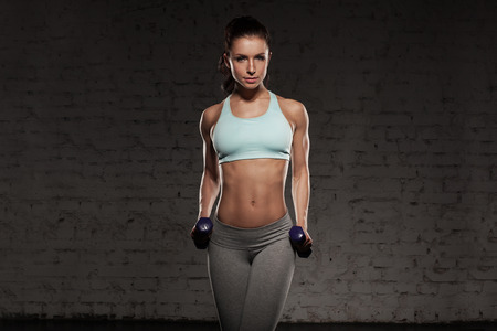 abs: Fitness female woman with muscular body, do her workout with dumbbells