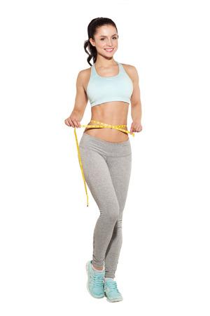 pérdida de peso, muchacha de los deportes que mide su cintura, entrenamiento en el gimnasio, abdominales entrenamiento Foto de archivo