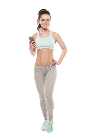 sports training: fitness girl with a smartphone on a white background, enjoys sports training, gym workout