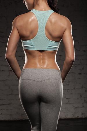 musculoso: la parte posterior de la mujer de los deportes en el entrenamiento, fitness chica con cuerpo musculoso, hacer su entrenamiento
