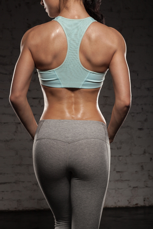the back of sports women on training, fitness girl with muscular body, do her workout Stock Photo