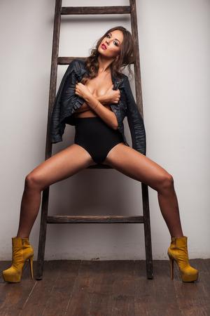 mujeres desnudas: hermosa mujer en topless sexy en la chaqueta de cuero cerca de la escalera, en las botas