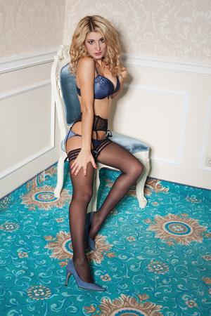 mujer desnuda sentada: retrato de la hermosa mujer joven atractiva en ropa interior atractiva azul que se sienta en la silla Foto de archivo