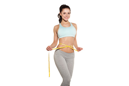 body shape: weight loss, sports girl measuring her waist, training in the gym, workout abdominals Stock Photo
