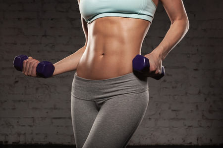 the female: Fitness female woman with muscular body, do her workout with dumbbells, abs, abdominals Stock Photo
