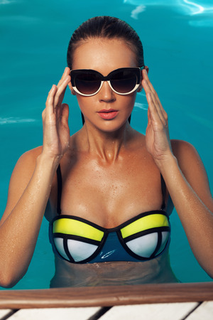 vacation summer: tanned woman in swimsuit and sunglasses swimming in the pool