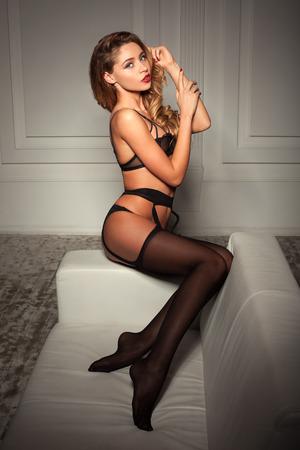 sexy nackte frau: sexy Frau in verf�hrerische schwarzen Dessous sitzt auf einer Couch in Str�mpfen