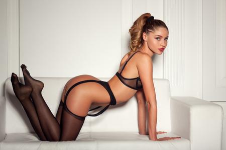 young sex: сексуальная женщина в соблазнительной черный белье, сидя на диване в чулках