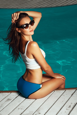 tans: woman near the pool, wearing glasses and swimsuit, tans and relaxing on vacation, healthy athletic body Stock Photo