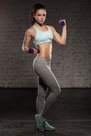 Fitness female woman with muscular body, do her workout with dumbbells