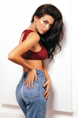 portrait of a beautiful brunette in a sexy bra and jeans, beautiful makeup and hairstyle