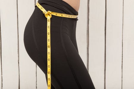 Slim young woman measuring her thin waist with a tape measure, close up Archivio Fotografico