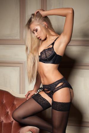 girls naked: сексуальная женщина в соблазнительной черный белье, сидя на диване в чулках