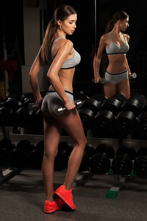 athletic body: fitness woman with a dumbbell in the gym, athletic body