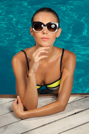 hot girl lying: woman near the pool, wearing glasses and swimsuit, tans and relaxing on vacation, healthy athletic body Stock Photo