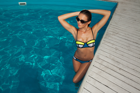 woman near the pool, wearing glasses and swimsuit, tans and relaxing on vacation, healthy athletic body Archivio Fotografico