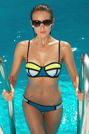 athletic body: woman near the pool, wearing glasses and swimsuit, tans and relaxing on vacation, healthy athletic body Stock Photo