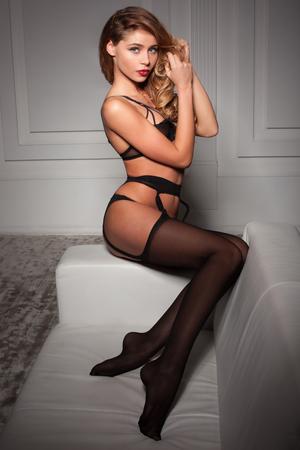 schwarze frau nackt: sexy Frau in verführerische schwarzen Dessous sitzt auf einer Couch in Strümpfen