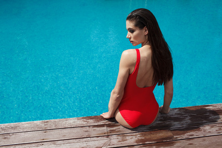 mujer bonita: woman in red swimsuit sitting near the pool, relaxing in spa