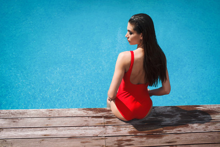 woman in red swimsuit sitting near the pool, summer tan Archivio Fotografico