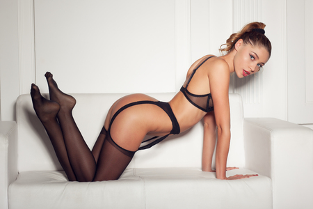 beautiful naked woman: sexy woman in seductive black lingerie sitting on a couch in stockings