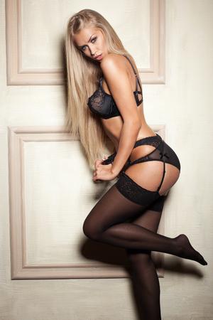 mujeres eroticas: Mujer atractiva en ropa interior negro seductora en las medias Foto de archivo