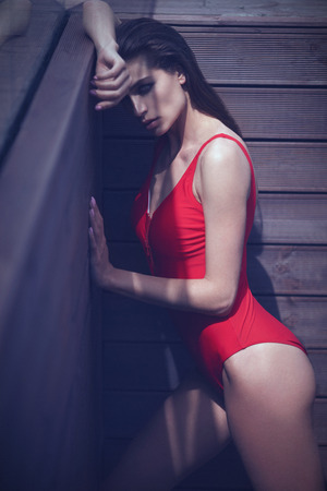 sexy woman: sexy woman in red swimsuit posing near the wooden wall