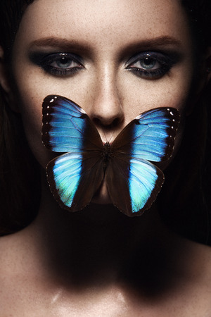 Close up portrait of girl with beautiful makeup. Blue exotic butterfly. Freckled face Archivio Fotografico