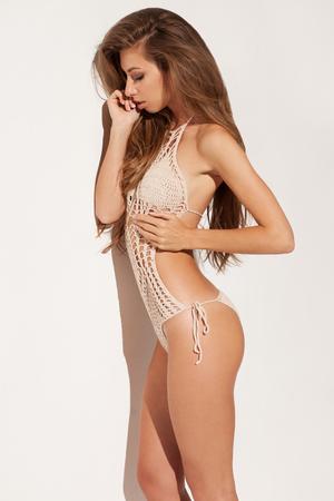 cuerpo femenino: Lanzamiento de la manera de la mujer joven atractiva en un traje de baño de punto. Tocar hermoso pelo largo y oscuro sobre fondo blanco aisladas