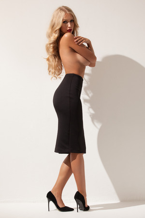 Sexy woman with long hair, legs, perfect skin and awesome body is posing topless in studio, wearing black expensive shoes and skirt