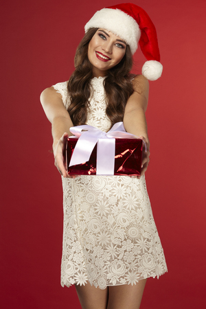 Woman with christmas box gift in Santa hat , with curly hair