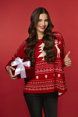 beautiful woman with a Christmas gift box, curly brunette woman in a warm sweater, on red background