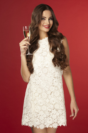beautiful girl in a white dress drinking champagne, new year, on a red background