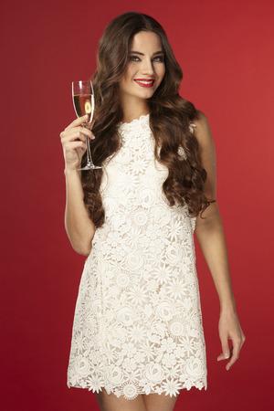 Bella ragazza in un vestito bianco a bere champagne, anno nuovo, su uno sfondo rosso Archivio Fotografico - 65142256