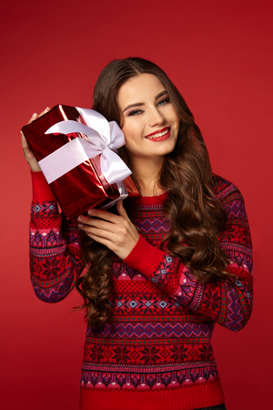 beautiful woman with a Christmas box gift, curly brunette woman in a warm sweater, on red background, new year