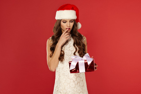 Woman with christmas box gift in Santa hat , with curly hair, new Year