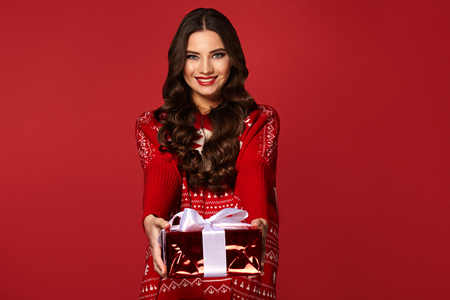 Woman with christmas box gift ,pretty girl in a warm sweater, with curly hair, new Year