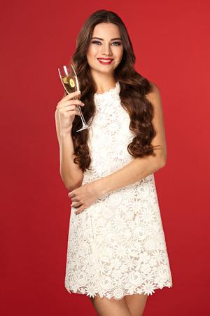 Bella ragazza in un vestito bianco a bere champagne, anno nuovo, su uno sfondo rosso Archivio Fotografico - 67473679