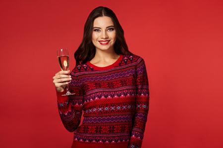 Ritratto di una bella donna che indossa maglione caldo sorridente, bevendo champagne con gli occhiali, anno nuovo Archivio Fotografico - 69142165