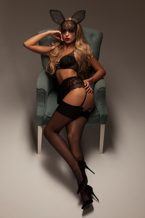 nude blonde girl: Stylish sexy blonde girl in a black lingerie, mask, stockings and garters isolated on a gray background