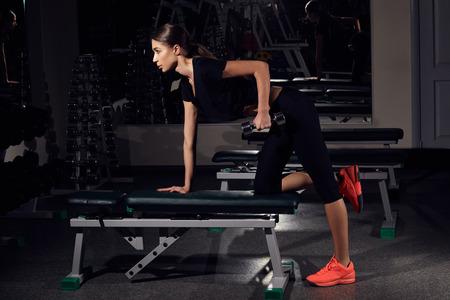 Fitness donna pompare i muscoli con manubri in palestra Archivio Fotografico - 70072950