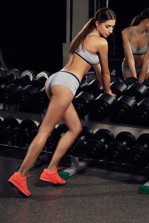 forme et sante: Stretching après une grande séance d'entraînement. Jeune femme belle en tenue de sport au gymnase. la santé de remise en forme