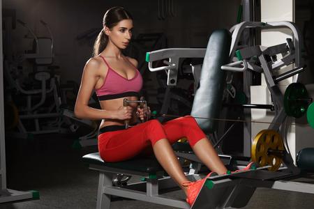 La giovane donna di forma fisica esegue l'esercizio con la macchina di esercizio in palestra Archivio Fotografico - 94477922