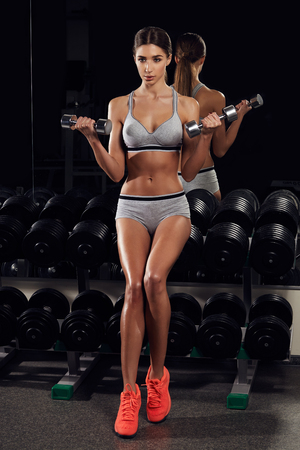 fitness woman pumping up muscles with dumbbells in in gym