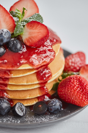 Pancakes close up, with fresh strawberry, blueberries, mint and jam on a white background