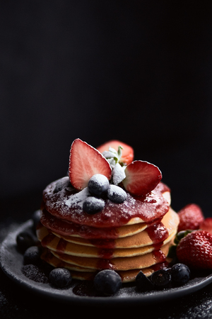 Pancakes close up, with fresh strawberry, blueberries, mint and jam on a black background