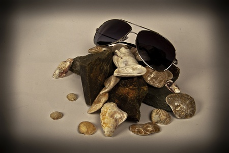 Sunglasses atop a pile of stones and shells.