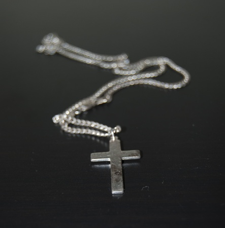 photo of accessories: sterling silver crucifix on black background showing signs of decay Stock Photo